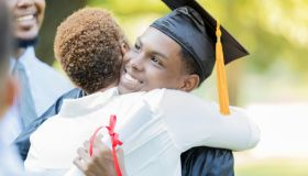 Proud mom hugs her son after graduation