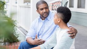 Concerned father sits on porch with preteen son
