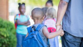 African American preschool age little boy holds his father's hand while walking to first day of kindergarten