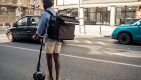 Young African Delivery Man Riding Electric Scooter In the City