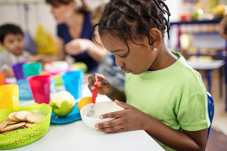 Cute girl eating from bowl by in preschool
