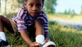 Boy Tying His Tennis Shoe