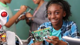 Junior high school age school students build robot in technology, engineering class.