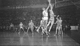 Basketball Players Jump for Ball
