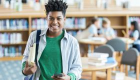 Confident teenage boy checks books out from the library