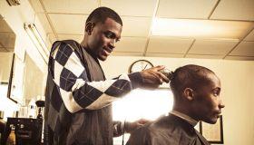 Barber in traditional barber shop shaving man's head