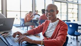 Smiling bald young woman using laptop in classroom