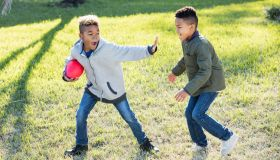 Two boys playing football in back yard