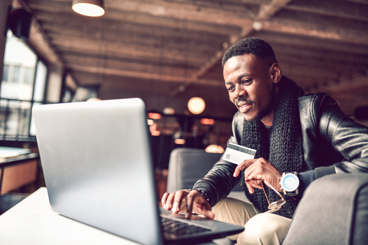 Happy African Male Online Shopping In Coffee Bar
