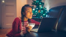 African American woman online Christmas shopping at home