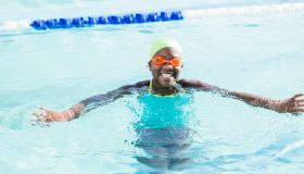 African-American girl with swimming cap, googles in pool