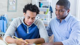 Confident father helps teenage son with homework