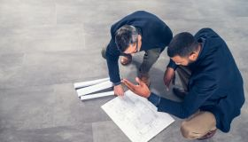 Architects talking about blueprints while crouching on the floor