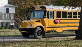 A Large Yellow School Bus Stops To Drop Off Students At Their Home