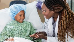 Doctor in hospital talking to child patient