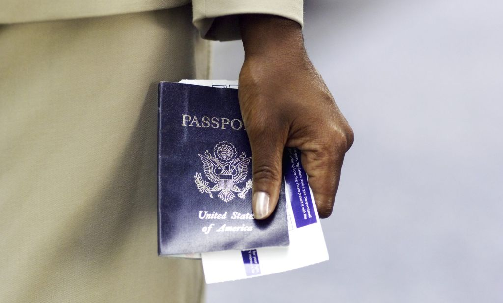 close up of businesswoman's hand holding passport and ticket