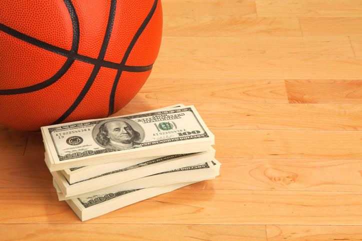 High Angle View Of Basketball By Us Currency On Hardwood Floor