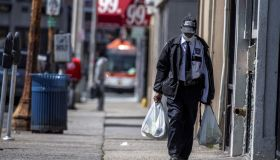 A Man Wearing A Security Guard Uniform and a Mask Walks in Hempstead, New York Carrying Groceries