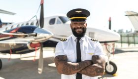 Portrait of pilot in front of airplane