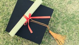 Close-Up Of Mortarboard And Diploma On Grassy Field