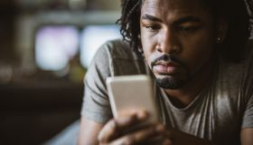 Young black man text messaging on smart phone at home.