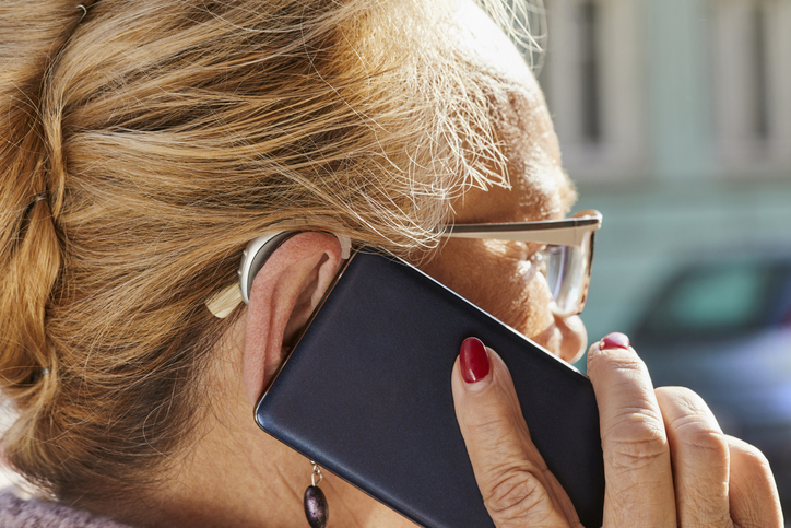 Close-up of senior woman with hearing aid using smartphone