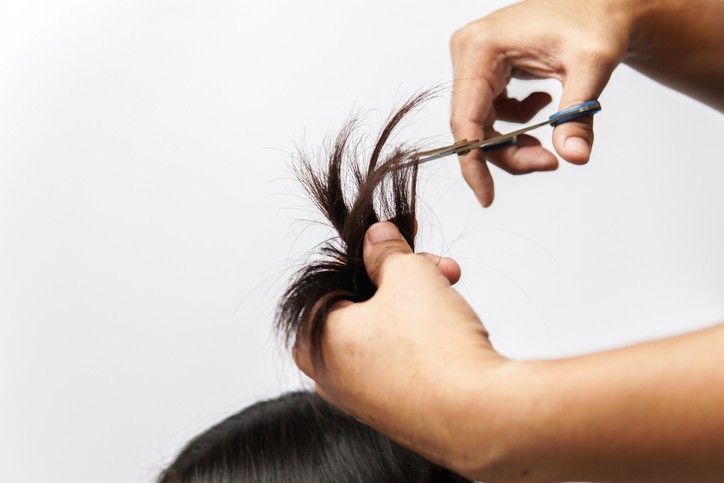Close-Up Of Man Cutting Hair Of Woman Over White Background