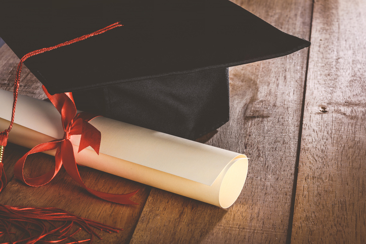 Close-Up Of Degree With Mortarboard On Table