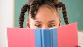African American girl reading book in classroom