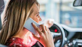 Young woman talking on phone while driving a car.
