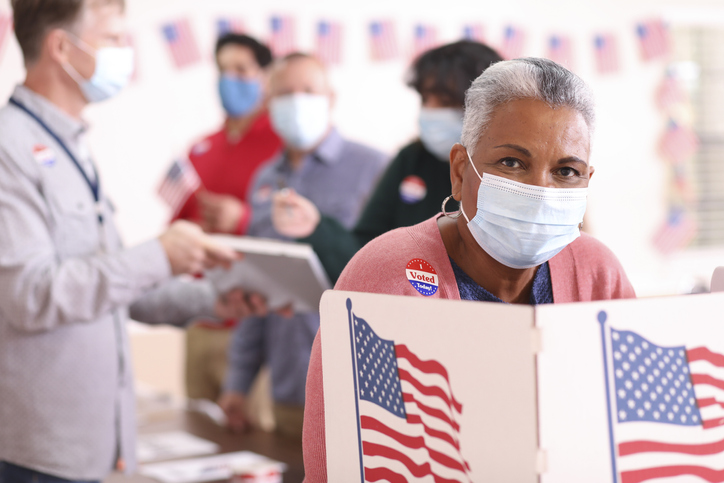Senior adult, African descent woman votes in USA election wearing mask.