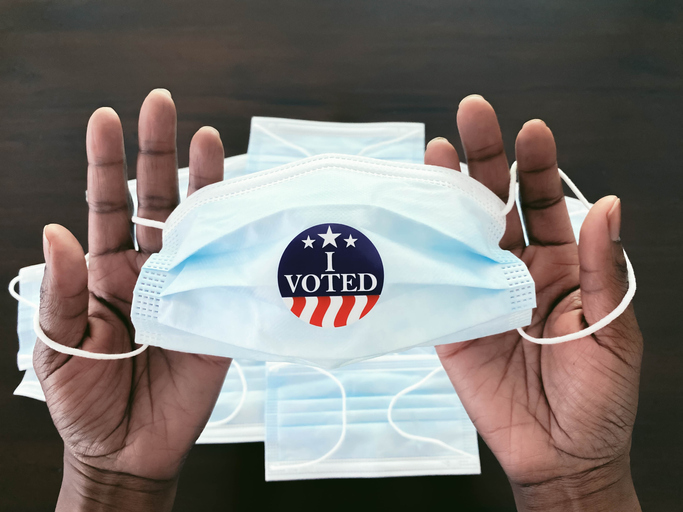 """Woman Holds Face Mask With """"I Voted"""" Sticker"""