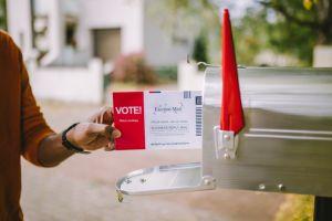 Man putting voting ballot to mailbox.