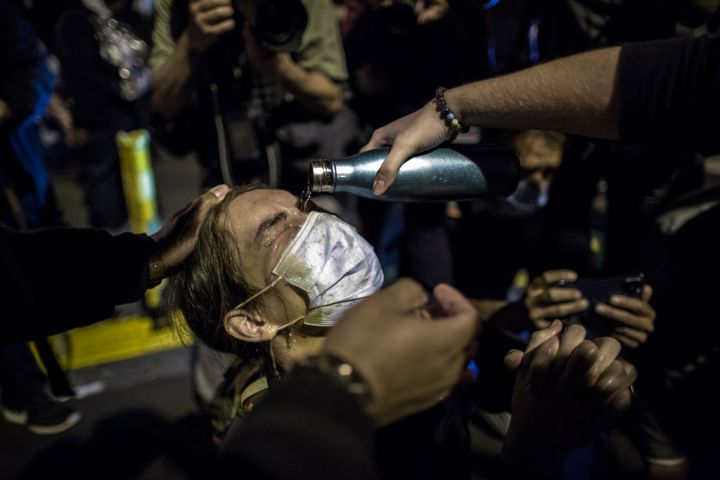 An anti-Trump demonstrator has her eyes rinsed after police...