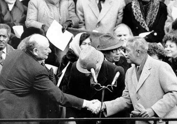 Dinkins at his Mayoral Inauguration on January 2, 1990, shaking hands with former Mayor Ed Koch.