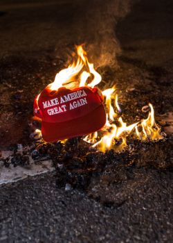 Black Lives Matter protesters burn a Trump Train hat prior...