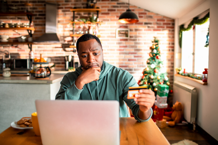 Young man doing online Christmas shopping