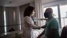 Doctor listening to patient's heartbeat during home visit - wearing face mask