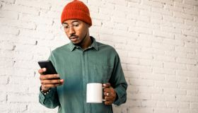 Man with coffee cup using smart phone against white brick wall