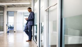 Businessman checking mobile device in modern business office