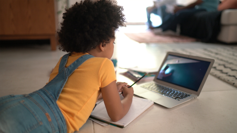 Rear view of a elementary age girl studying watching online classes at home