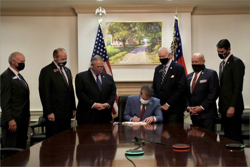 Georgia Gov. Brian Kemp signs voter suppression laws in front of painting of slavery plantation