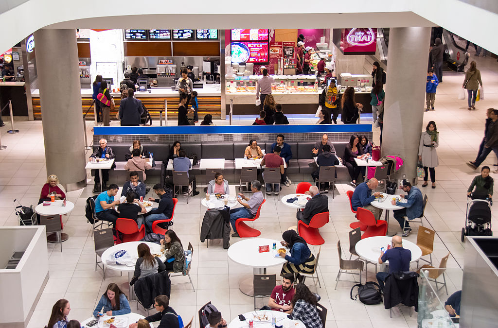 People at a food court inside a mall, with some people...