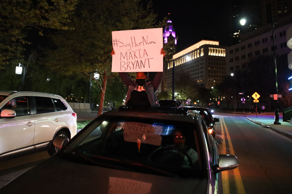 A protester holds a sign out of a car during the MaKhia...