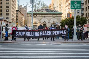 Participants seen holding a banner reading STOP KILLING...