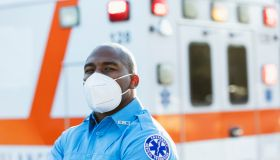 Paramedic in front of ambulance, with face mask