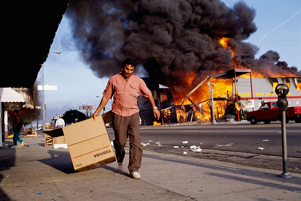 Man Walking Past Burning Building