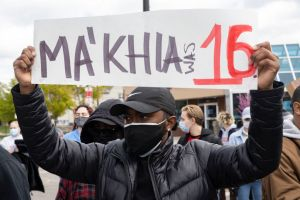Black Lives Matter activist holds a placard protesting the...