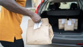 Close up of a curbside service staff holding paper bags
