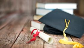 Graduation Cap and Diploma Concept on a Wood Background